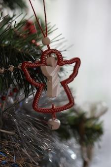 Decoração da árvore de natal de um anjo pendurado nos galhos