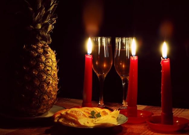 Decoração de abacaxi com três velas vermelhas acesas e taça de vinho