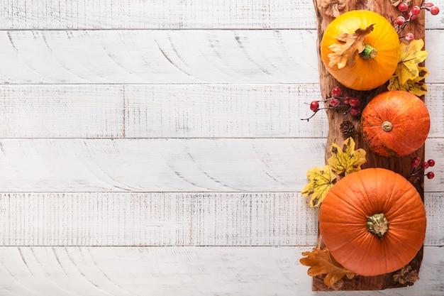 Decoração de abóboras, frutas e folhas em fundo branco de madeira rústica. conceito de dia de ação de graças ou halloween. composição festiva de outono de vista superior com espaço de cópia.