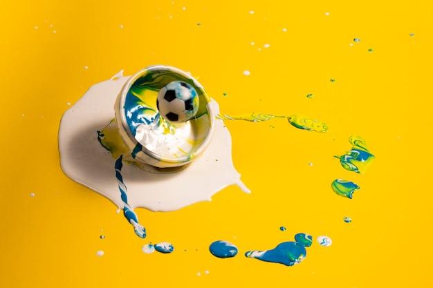 Decoração de alto ângulo com tinta amarela e bola de futebol