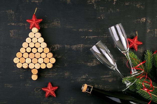 Decoração de ano novo com árvore de natal feita de rolhas de vinho e uma garrafa de champanhe. fundo de natal. vista do topo.