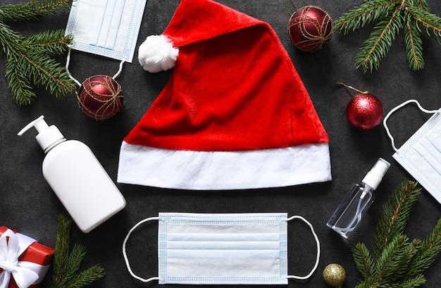 Decoração de ano novo com chapéu de papai noel e máscara médica e presentes.