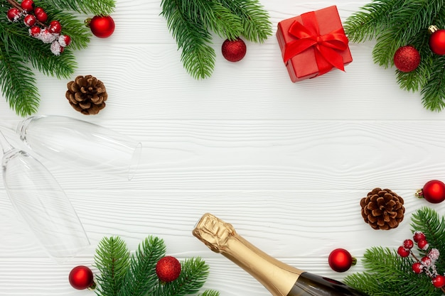 Decoração de ano novo com garrafa de champanhe e ramos de pinheiro