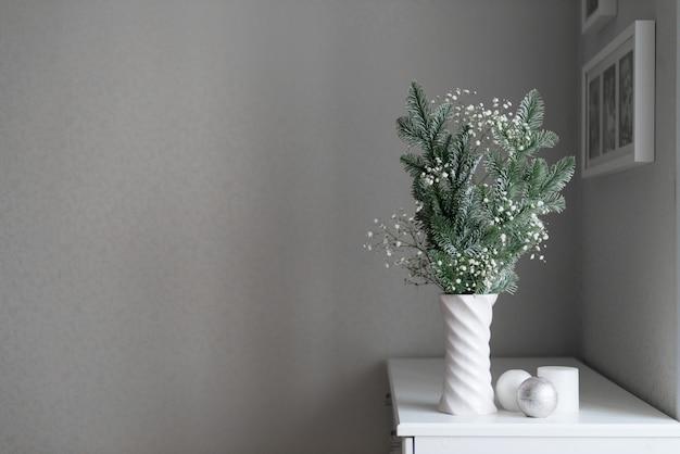 Decoração de ano novo, composição minimalista de galhos de pinheiro e gipsófila em vaso