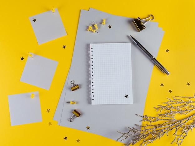 Decoração de ano novo da mesa de escritório amarela com caderno em branco e outros materiais de escritório