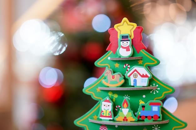 Decoração de artesanato de papel de árvore de natal na mesa de madeira com borrão de árvore de natal grande atrás.