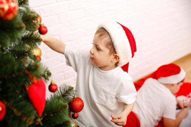 Decoração de árvore de natal com enfeites e luzes criança feliz