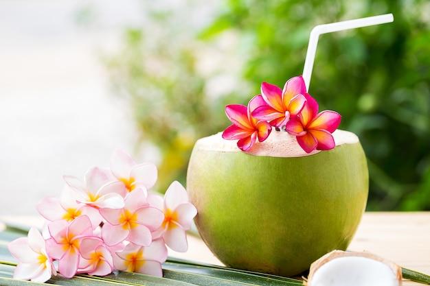 Decoração de bebida de coco com flor de fangipani.