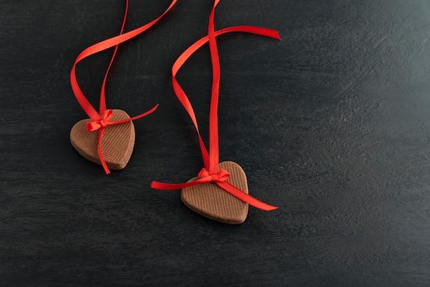 Decoração de biscoitos de gengibre de dia dos namorados. biscoitos com fitas vermelhas em fundo preto em forma de coração.