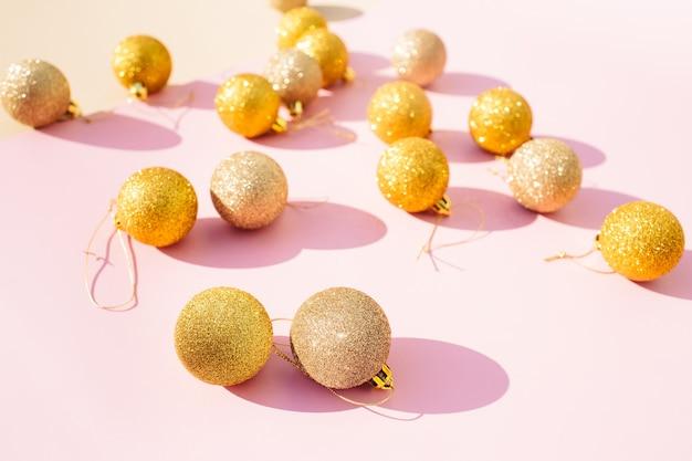 Decoração de bolas de natal de glitter dourados em fundo rosa. cartão de ano novo.