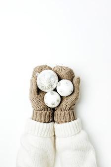 Decoração de bolas de natal nas mãos femininas em luvas de malha na superfície branca. vista do topo