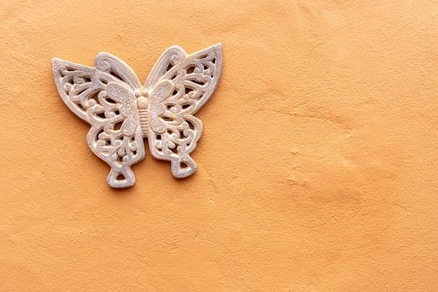 Decoração de borboleta em parede amarela áspera