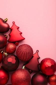 Decoração de brinquedos de natal vermelha em fundo rosa com espaço de cópia. cartão de ano novo. estilo mínimo. postura plana. foto vertical