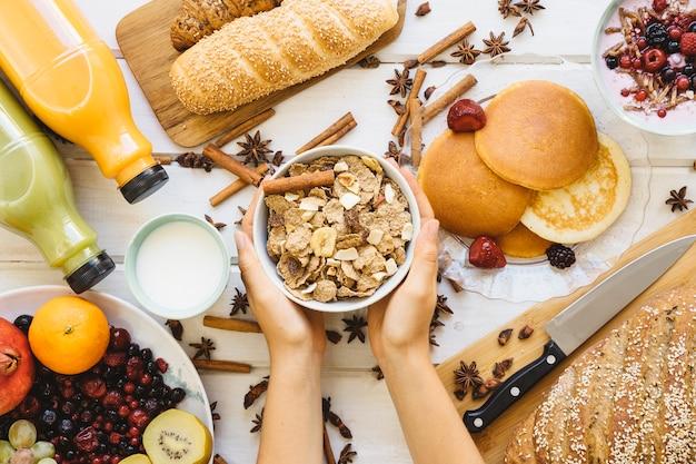 Decoração de café da manhã com mãos segurando cereais