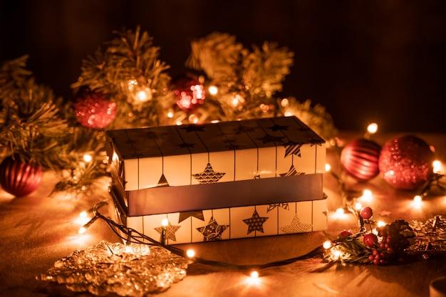 Decoração de caixas de presente de natal com luzes de árvore e vela de natal em cima da mesa de madeira com luzes de bokeh