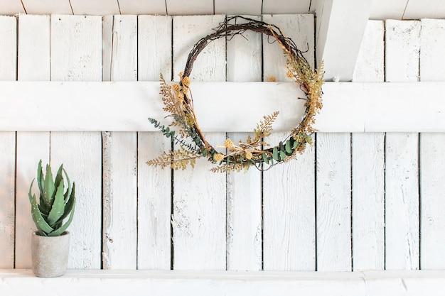 Decoração de casa com uma composição mínima feita de grinalda de flores secas e pequeno vaso cerâmico cilíndrico de concreto com planta aloe.