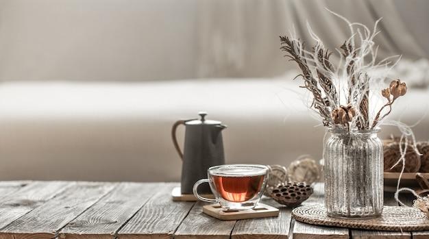 Decoração de casa lindo vaso com flores e uma xícara de chá.