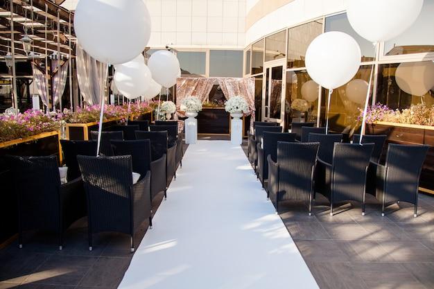 Decoração de casamento, cadeiras para convidados, anéis de casamento e enormes balões brancos