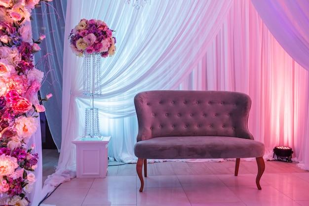 Decoração de casamento com sofá retrô clássico e brancas, flores cor de rosa.