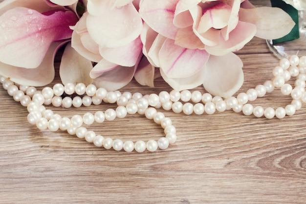 Decoração de casamento - flores de magnólia com colar de pérolas na mesa de madeira