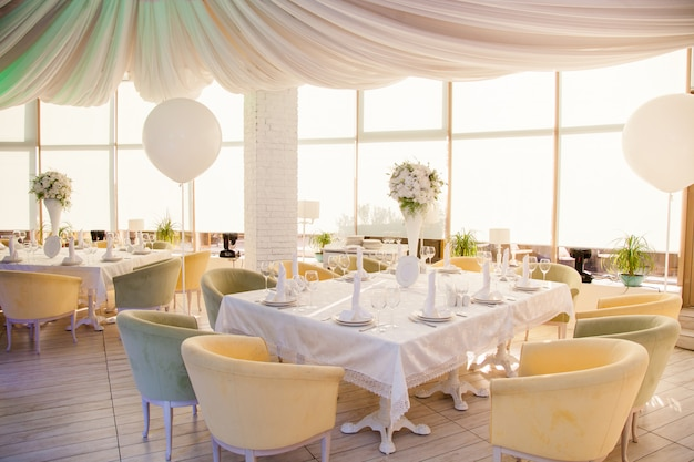 Decoração de casamento, mesas de casamento no restaurante com flores brancas e enormes balões brancos