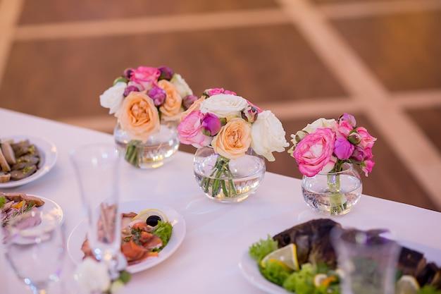 Decoração de casamento na mesa. arranjos florais e decoração. arranjo de flores rosa e brancas no restaurante para evento de casamento de luxo