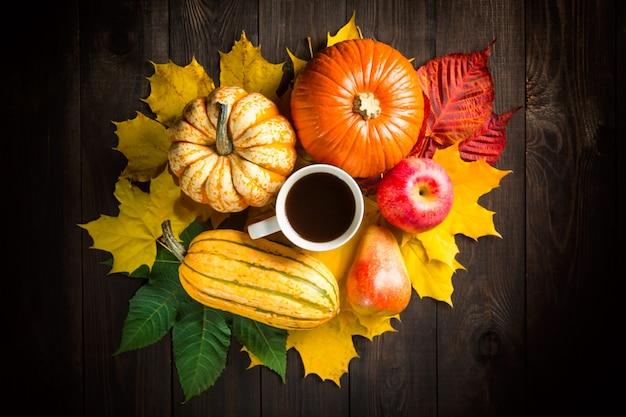 Decoração de cenário outono com abóboras, medula, maçã, pêra, xícara de café e folhas coloridas em fundo escuro de madeira.