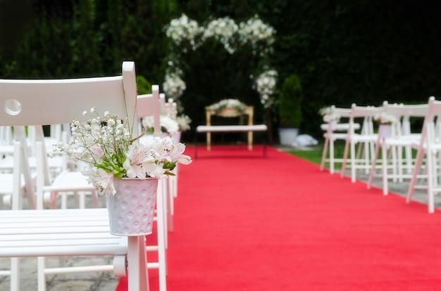 Decoração de cerimônia de casamento bonito, altar rústico decorado com flores de lírios, alstroemerias e crisântemos atrás da parede de hera, tapete vermelho com cadeiras brancas. conceito de dia do casamento. espaço para texto.