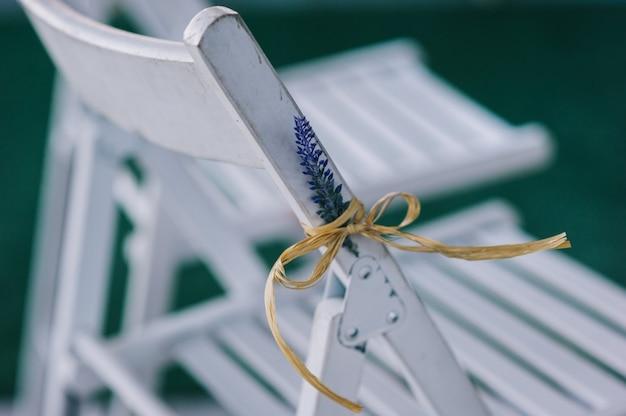 Decoração de cerimônia de casamento. cadeiras de madeira brancas com flores de lavanda.