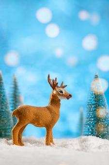 Decoração de cervo de brinquedo com árvores de natal e neve