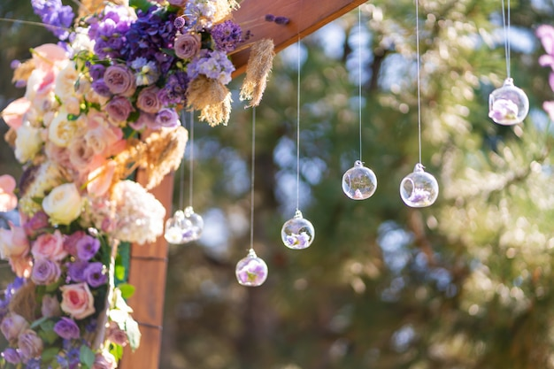 Decoração de close-up com flores frescas de locais. arco de casamento decorado com flores frescas e bolas de vidro penduradas