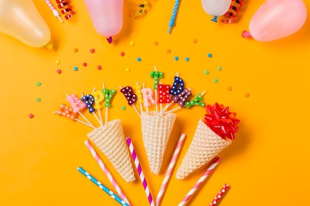 Decoração de cone decorativo feliz aniversário no pano de fundo amarelo