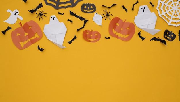 Decoração de corte de papel artesanal de halloween em fundo amarelo. fundo de dia das bruxas. copie o espaço