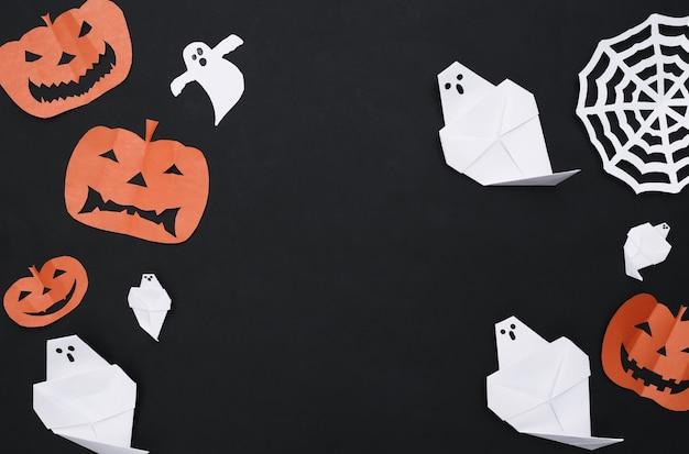Decoração de corte de papel artesanal de halloween em fundo preto. fundo de dia das bruxas. copie o espaço