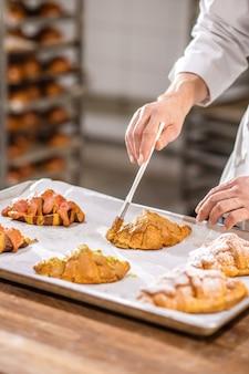 Decoração de croissant. mão de um experiente chef de confeitaria com pincel tocando croissants na bandeja, aplicando esmalte de massa