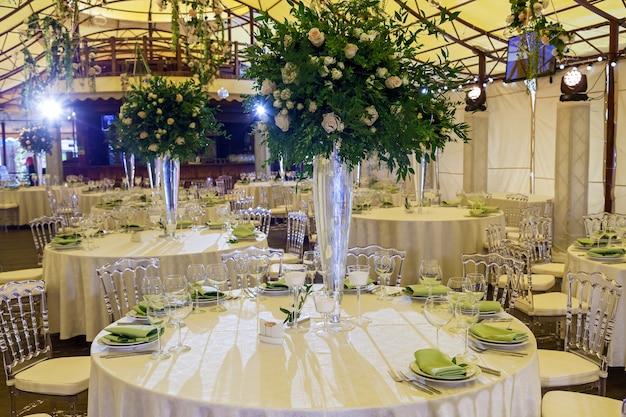 Decoração de design e decoração de festa de casamento com rosas brancas, folhas verdes, velas e buquês de flores