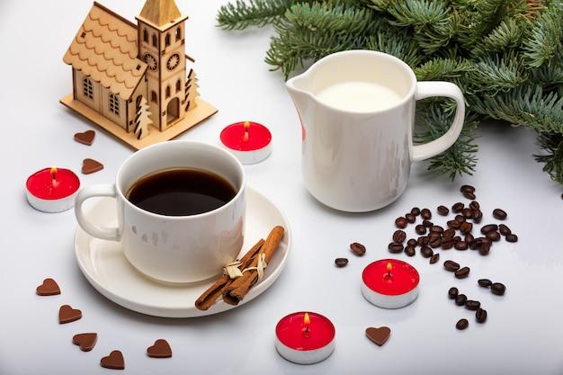 Decoração de dia dos namorados com uma xícara de café expresso com leite, pinheiros, velas vermelhas e chocolate