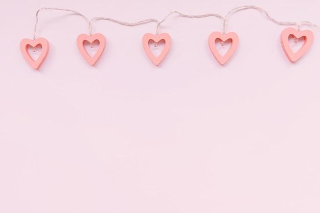 Decoração de dia dos namorados - luzes em forma de coração em um fundo rosa