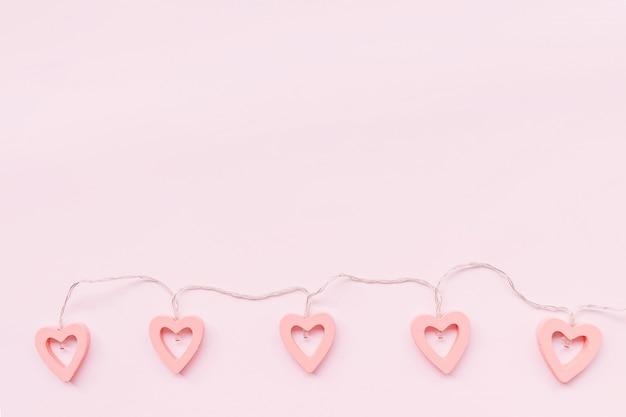Decoração de dia dos namorados. luzes em forma de coração em um fundo rosa