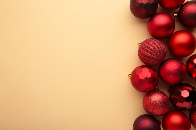 Decoração de enfeites de natal vermelha em fundo bege com espaço de cópia. cartão de ano novo. estilo mínimo. postura plana.