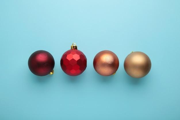 Decoração de enfeites de natal vermelha sobre fundo azul com espaço de cópia. cartão de ano novo. estilo mínimo. postura plana. vista do topo