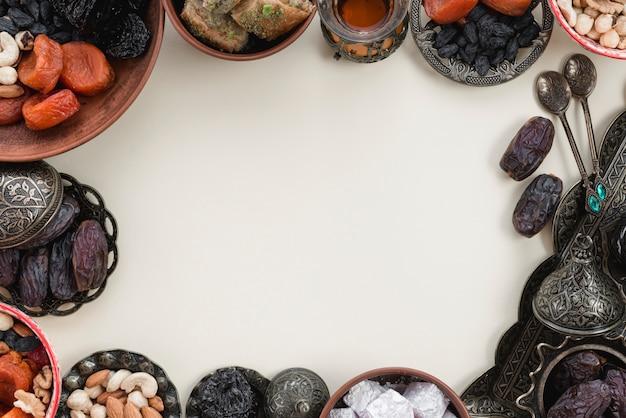 Decoração de feriados orientais com frutas de datas; datas; lukum e nozes no fundo branco com espaço no centro para escrever o texto