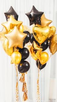 Decoração de festa de boas-vindas. redondo dourado e preto, coração, balões em forma de estrela em branco.
