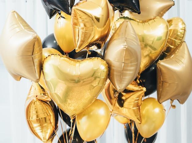 Decoração de festa. interior festivo. close up de balões redondos dourados e pretos, coração, estrela em forma de branco.