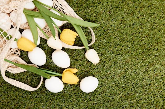 Decoração de flores de ovos de páscoa em grama de tradição de feriado no fundo