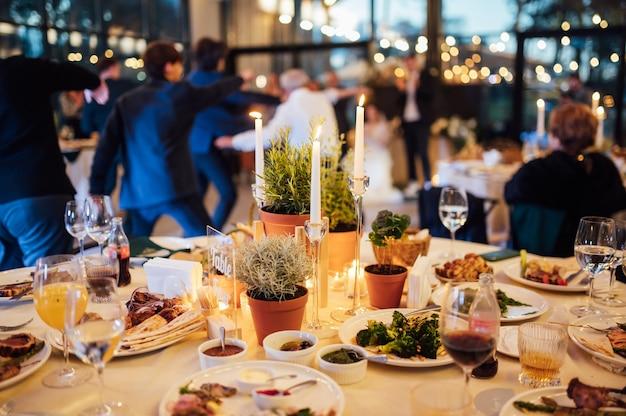 Decoração de flores e velas para um casamento no contexto de convidados dançando