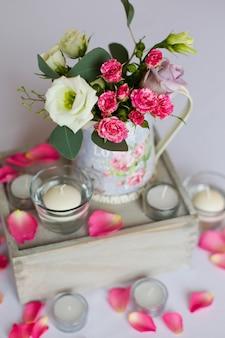 Decoração de flores em vaso de ferro em cima da mesa e velas planas brancas