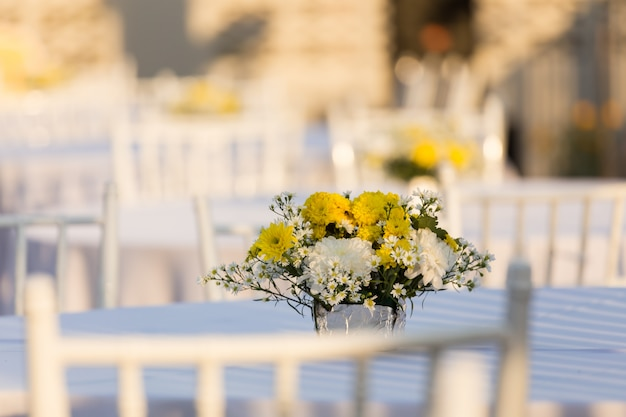 Decoração de flores na mesa branca ao ar livre na recepção do casamento