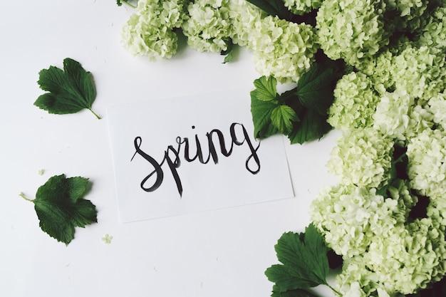 Decoração de flores verdes e folhas com inscrição caligráfica