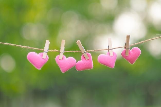 Decoração de forma de coração rosa pendurado na linha com espaço de cópia
